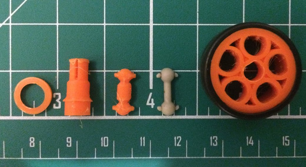 Assorted small 3D printed parts and a wheel